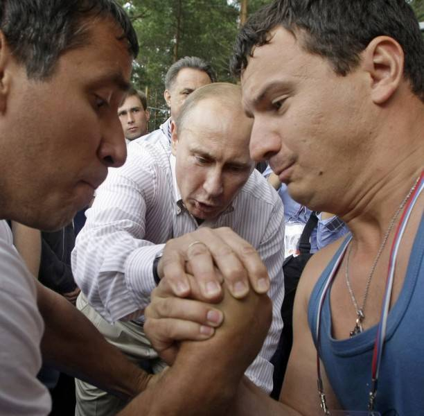 still-hes-not-always-the-one-in-the-arena-here-he-adjudicates-an-arm-wrestling-match-between-two-competitors-at-a-kremlin-youth-camp