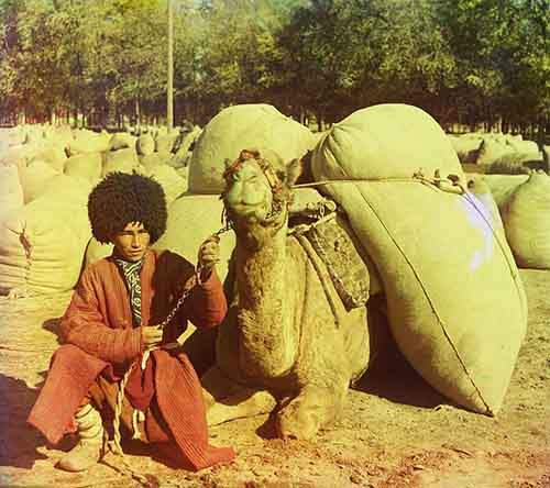a-man-sits-on-the-ground-next-to-his-camel-loaded-with-packs