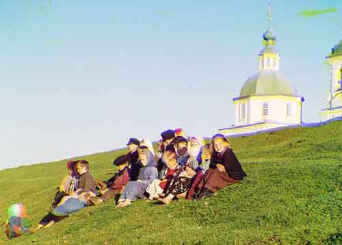children-sit-near-a-church-on-white-lake-in-russia