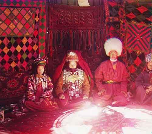 four-people-sit-on-a-carpet-in-front-of-a-backdrop-of-textiles