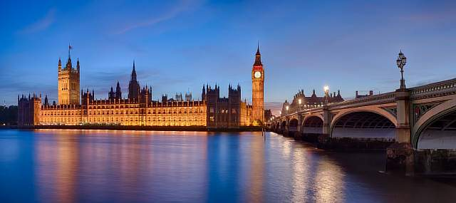 a-panoramic-view-of-the-london-parliament-big-ben-and-the-westminster-bridge-viewed-from-across-the-thames-river-at-dusk