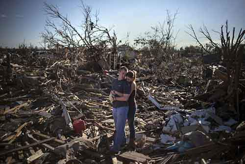 Danielle Stephan holds boyfriend Thomas Layton as they pause between salvaging through the remains of a family member's home one day after a tornado devastated the town Moore, Oklahoma