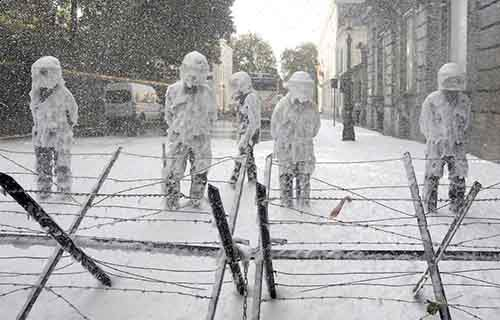 Belgian riot police are covered with foam sprayed by Belgian firefighters during a protest for better work conditions in central Brussels