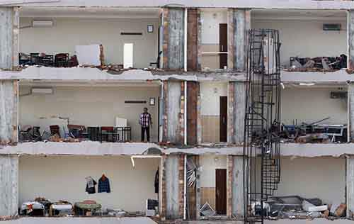 A man checks an apartment on a damaged building at the site of a blast in Reyhanli
