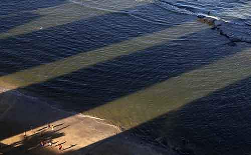 Men play soccer between the shadows of buildings in Boa Viagem Beach in Recife