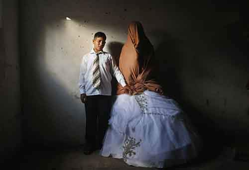 Palestinian groom Ahmed Soboh and his bride Tala stand inside Tala's house which damaged during Israeli strike in 2009, during wedding party in Beit Lahiya