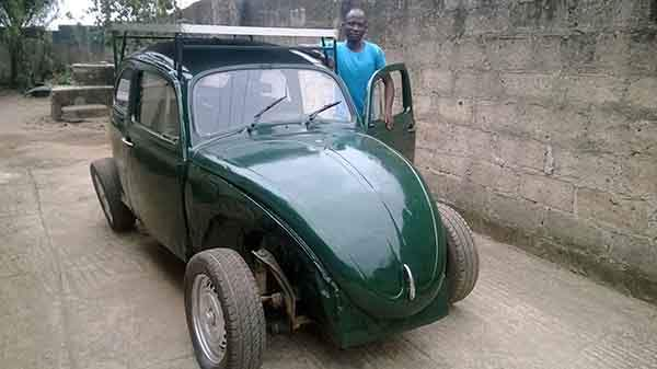 Nigerian university student with the solar powered car he created.