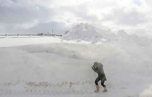 a-person-walks-past-a-snowdrift-in-northern-ireland