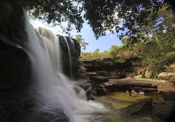 tourists-bathe-at-the-el-cuarzo-waterfall-locally-referred-to-as-the-river-of-five-colors-in-cano-cristales-in-the-colombias-sierra-de-la-macarena-national-park