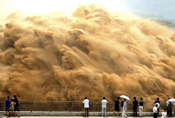 visitors-watch-water-gushing-from-the-section-of-the-xiaolangdi-reservoir-on-the-yellow-river-during-a-sand-washing-operation