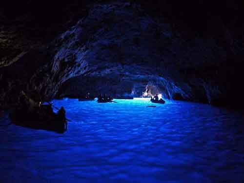 float-through-the-blue-grotto-a-sea-cave-in-capri-with-stunning-blue-light-reflected-off-of-the-water