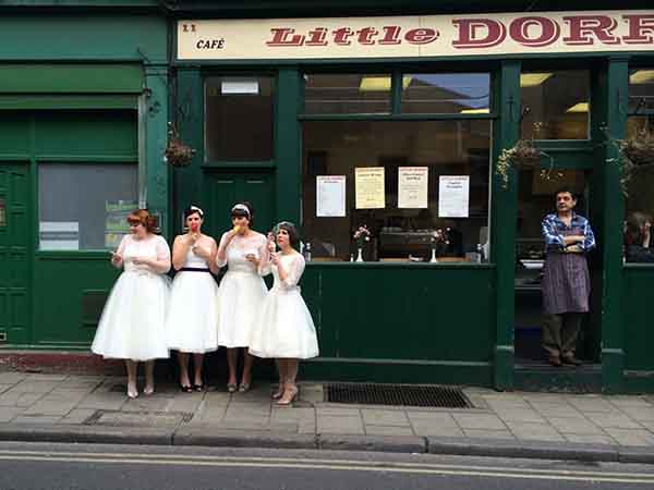 merit-prize-while-exploring-burrough-market-in-london-this-photographer-caught-these-four-women-dressed-in-vintage-white-dresses-eating-ice-cream-in-front-of-a-shop