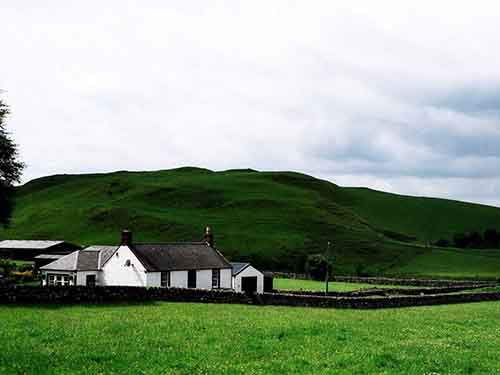 a-small-house-sits-at-the-foot-of-a-hill-in-lockerbie-scotland