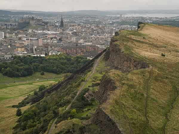 edinburgh-castle-sits-on-top-of-castle-rock-in-the-distance-as-seen-from-holyrood-park