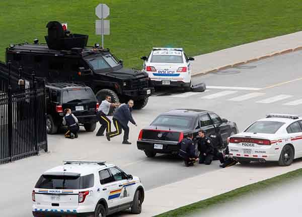 police-officers-take-cover-near-parliament-hill-following-a-shooting-in-ottawa-canada-on-october-22-one-soldier-was-fatally-shot