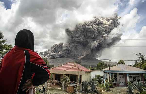 the-indonesian-volcano-mount-sinabung-erupted-in-mid-october-here-a-woman-in-the-village-of-karo-watched-the-dust-cloud