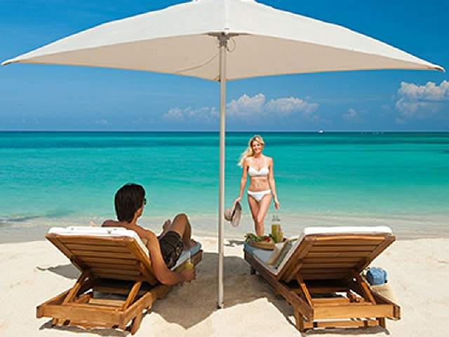 fantasy-guest-at-the-sandals-carlyle-inn-can-relax-on-cozy-lounge-chairs-on-a-beautiful-white-sand-beach