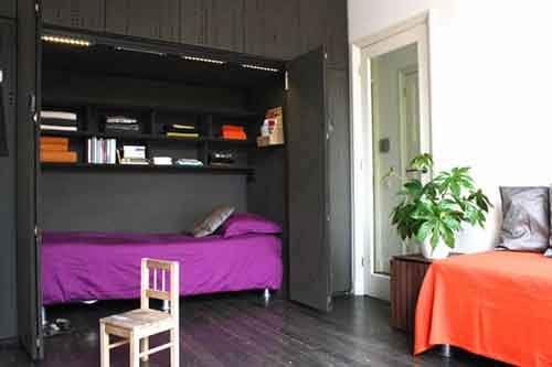 14914210-R3L8T8D-650-space-saver-beds-with-purple-bedding-and-built-in-bookshelves-also-cabinets-with-dark-wood-flooring-and-indoor-plant-plus-day-bed-bedding