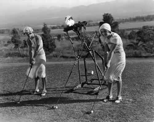 1925.-Two-ladies-improve-their-aim-by-taking-golf-lessons-from-a-robot-trainer.-1925