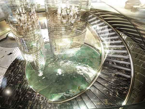 the-centerpiece-of-the-salon-is-a-huge-chandelier-surrounded-by-a-circular-staircase