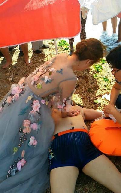Woman in wedding gown tries to resuscitate a drowned man. She's a nurse and happens to be shooting wedding photos nearby.