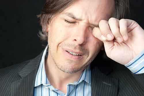 Close-up of a stressed businessman rubbing his eyes.
