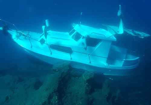 Kusadasi Ilgun, the sunken 6-meter (20-foot) plastic boat, lies in waters 3 meters (10 feet) deep just 20 meters (yards) off the eastern Greek island of Samos on Sunday, Nov. 1, 2015. Greek authorities say 11 more people have drown on the dangerous crossing from Turkey to Greece after the boat carrying nearly 30 refugees sank in heavy seas near the eastern island of Samos. (Alexis Malagaris/Samos Divers Association via AP)