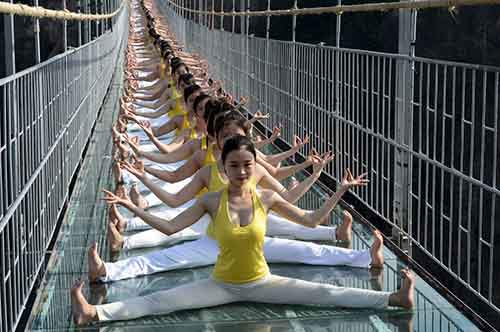 Women practice yoga during a performance on a glass bridge at the Shiniuzhai National Geo-park in Pingjiang county, Hunan province, China, November 5, 2015. About hundred yoga fans put on the show to promote the concept of green life and the idea of harmony between human and nature on Thursday, according to local media. REUTERS/China Daily CHINA OUT. NO COMMERCIAL OR EDITORIAL SALES IN CHINA. - RTX1UUWR