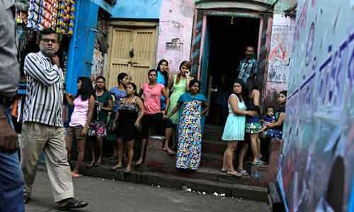 Girls stand outside the city's biggest red-light zone, Sonagachhi, and watch a rally demanding prostitution be made legal, in Kolkata, India, Saturday, Nov. 8, 2014. The rally was organized by Durbar Mahila Samanwaya Committee, a collective of 65,000 sex workers of West Bengal state fighting against stigma and for the rights of sex workers. (AP Photo/ Bikas Das)