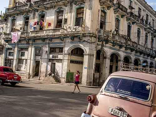 A street in Havana, with its dilapidated but architecturally rich buildings, and vintage American cars