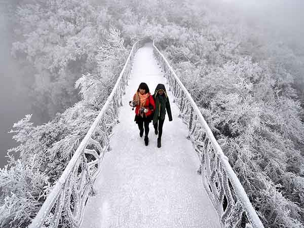 Tourists walk on a bridge covered by frosty fog on the Tianmen Mountain resort in Zhangjiajie, Hunan province