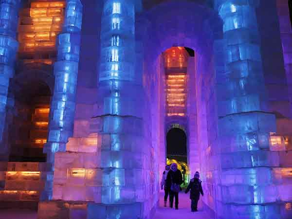 People visit ice sculptures illuminated by coloured lights during a trial operation ahead of the 31st Harbin International Ice and Snow Festival in the northern city of Harbin, Heilongjiang province, January 4, 2015.