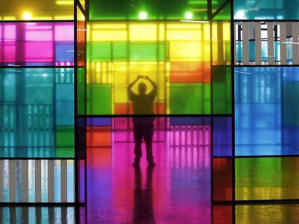 A man takes a picture of an art piece by French artist Daniel Buren