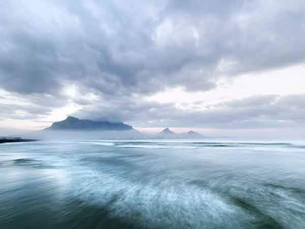 dramatically sweeping waves and billowing cloud formations paint this grey-green dawn over Cape Town and Table Mountain. Cape Town is still shrouded in early morning fog at the foot of the mountain, while the top of the mountain is wearing the dissipating clouds from the storm just passed