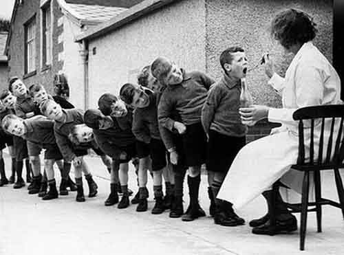 Boys lining up for Cod Liver Oil in the 1960s