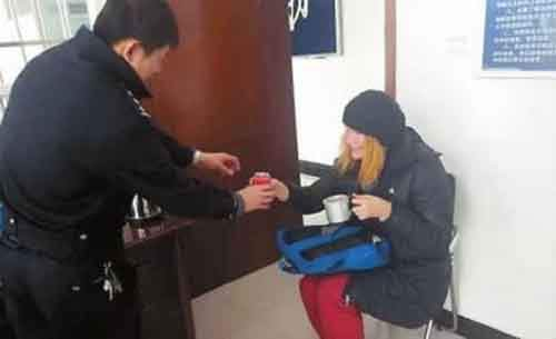 Chinese policeman offers a hot drink to a Russian woman