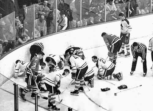 Ice Hockey players and referees searching for a contact lens in 1962