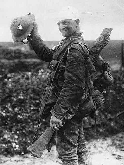 Lucky British soldier shows off his damaged helmet, 1918