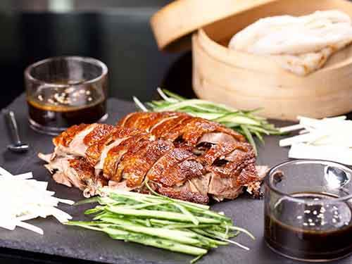 theres-peking-duck-wrapped-in-a-pancake-and-served-with-scallions-and-hoisin-saucejpg
