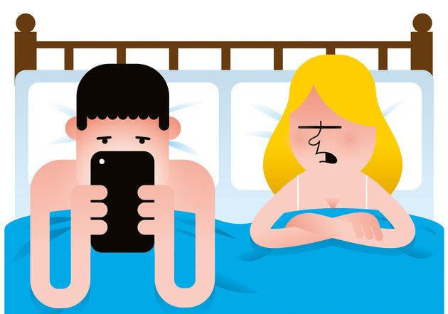 A man and woman in bed while the man is looking at a mobile device