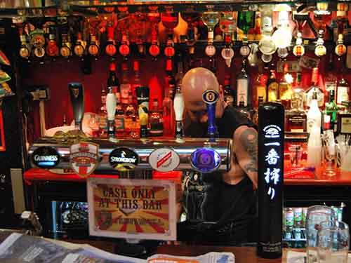tattooed bartender with beer