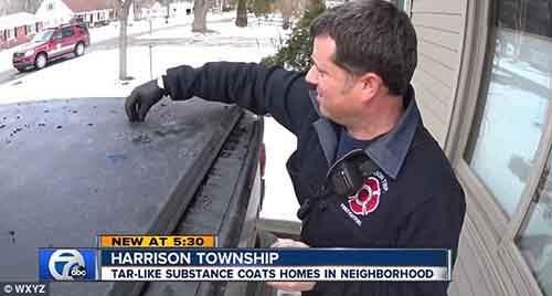 Мужчина пытается очистить машину от чёрной субстанции